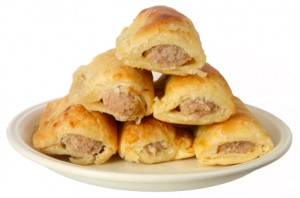 A plate stacked with festive sausage rolls.
